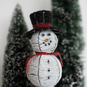 A snowman in front of evergreens
